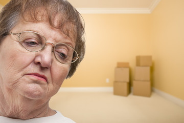 Sad Older Woman In Empty Room with Boxes