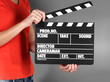 Movie production clapper board in hands on grey background
