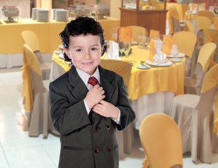 Elegant little boy clutching his tie in a restaurant