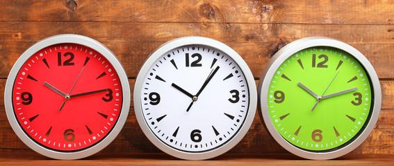 Round office clocks on wooden background