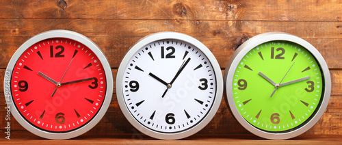 Round office clocks on wooden background