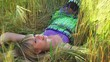 Young woman laying in a field of wheat
