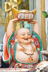 chinese smile statue with ancient money