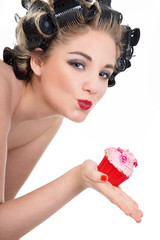 Junge Frau in Pin Up Style mit Cupcake küsst