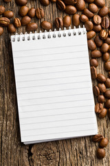 spiral notebook and coffee beans