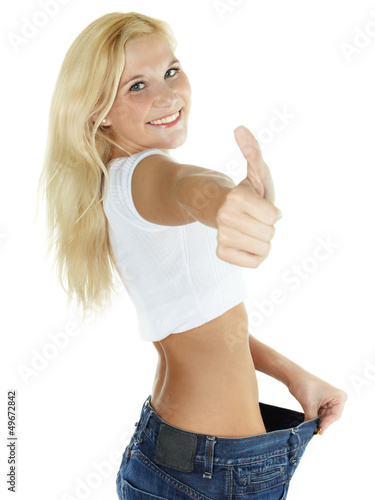 Beautiful girl is proud to lose weight - showing thumb up