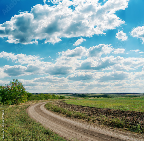 winding rural road to cloudy horizon