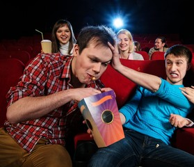 Impudent young man steal popcorn in cinema