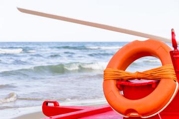 Orange Lifebuoy on a red Lifeguard Rowboat
