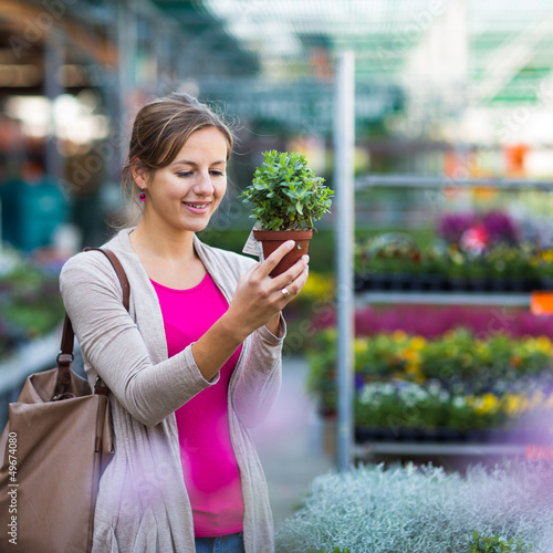 Young woman buying flowers at a garden center (color toned image