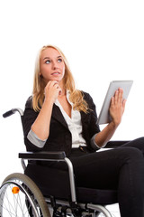 Blond girl sitting in a wheel chair with tablet PC