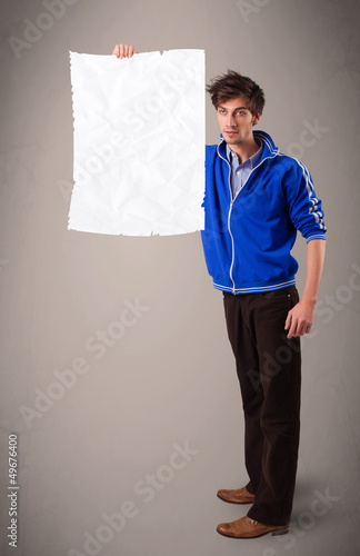 Young boy holding crumpled white paper copy space