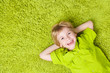 Happy child lying on the green carpet background. Boy smiling an