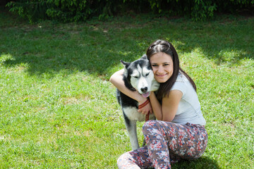 girl hugging her dog Siberian husky in yard