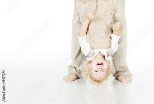Child standing head over heels. Funny up portrait. Parent legs.