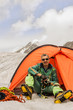 The climber in tent against Mountains Altai