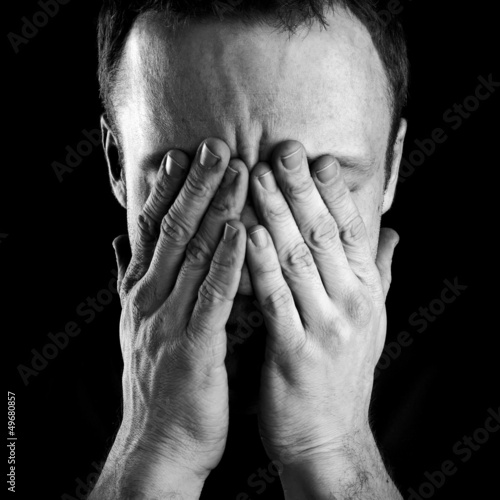 Portrait of stressed man covers his face with hands