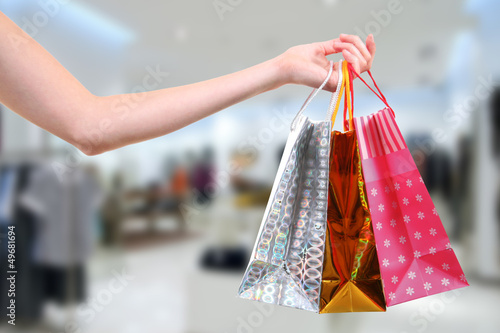 woman with shopping bags in clothes shop