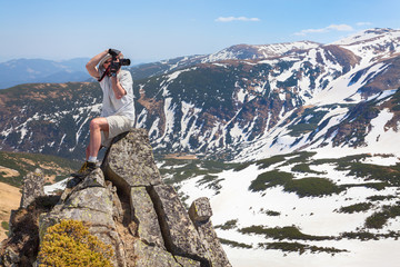 Photographer makes the photo in the mountains on the high rock