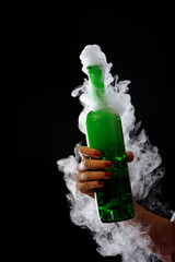 beautiful hand with green foggy bottle