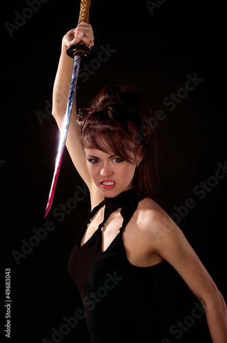Beautiful woman in black dress with katana sword