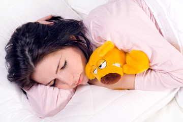 girl sleeping with teddy bear in bed