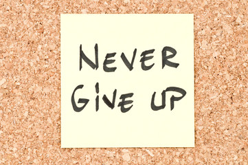 Never Give Up, handwritten on a sticky note