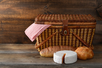 picnic basket with bread and cheese on wood