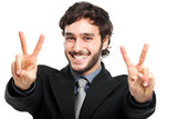 A businessman in a suit giving the victory sign