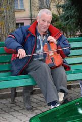 Уличный музыкант играет на скрипке