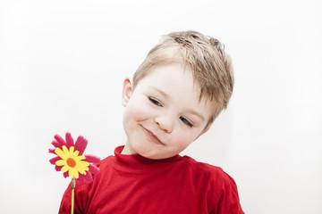 nachdenkliches Kind hält Blume