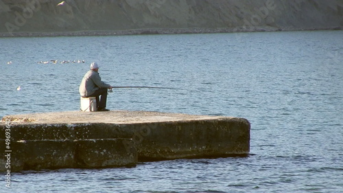 Senior adult man fishes from a pier.