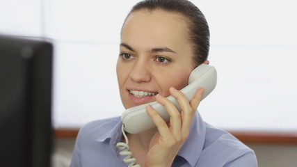 Woman talking on landline phone in front of the computer