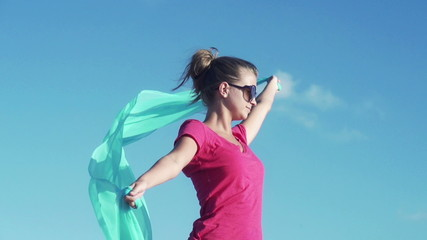 Woman with pareo against blue sky, super slow motion