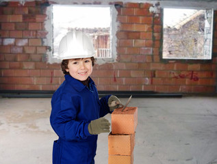 Happy little boy bricklayer