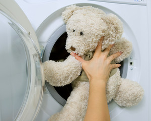 woman loading toy in the washing machine