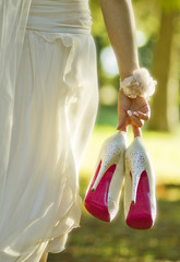 Bride with wedding shoes. Selective focus.