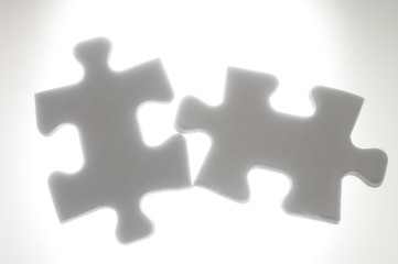 Connecting two puzzle pieces against the light.