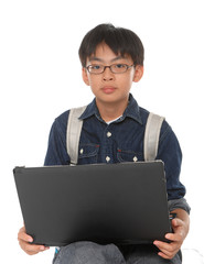 Young boy student with a school bag working on a laptop