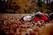 A woman lying on the ground hold an autumn leaf