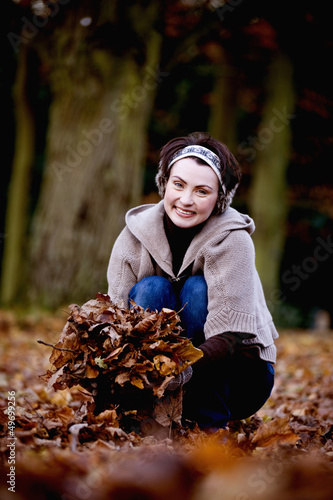 A woman gathering leaves in autumn time