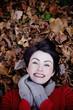 A woman lying amongst autumn leaves