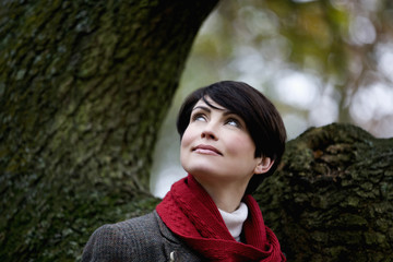 A woman standing next to a tree in autumn time, looking up