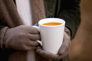 A woman holding a cup of soup in autumn time, close up