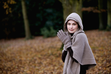 A woman rubbing her hands to keep warm in autumn time