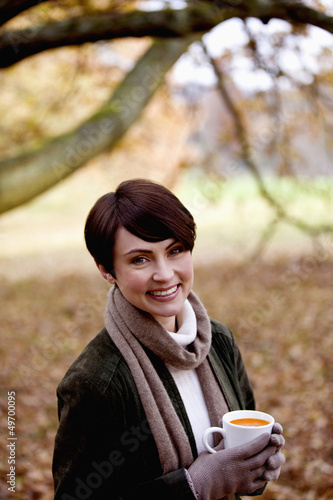 A woman holding a cup of soup in autumn time