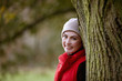 A woman leaning against a tree in autumn time, smiling