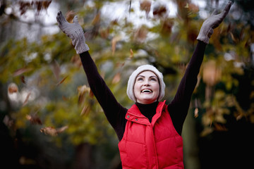 A woman catching falling autumn leaves