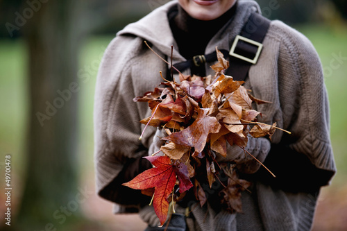 A woman holding a handful of autumn leaves