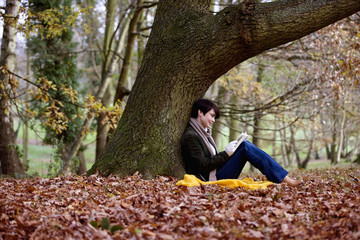 A woman sitting under a tree in autumn time, reading a book